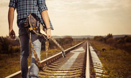 Photo for Young man with guitar on a railway to horizon sunset - Royalty Free Image