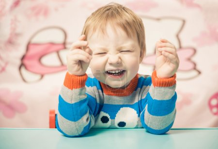 Photo for Little caucasian boy laughing at the table - Royalty Free Image
