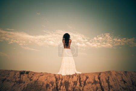 Photo pour Jeune brunet en robe blanche à sec colline coucher de soleil sur l'horizon - image libre de droit