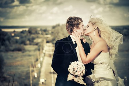 Photo for Young wedding couple kissing at windy countryside day - Royalty Free Image