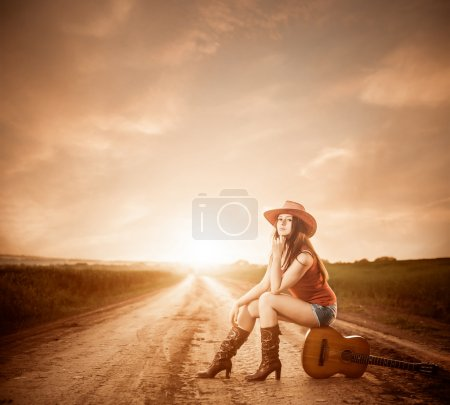 Photo for Young pretty woman in red hat sitting on guitar at sunset road to horizon - Royalty Free Image