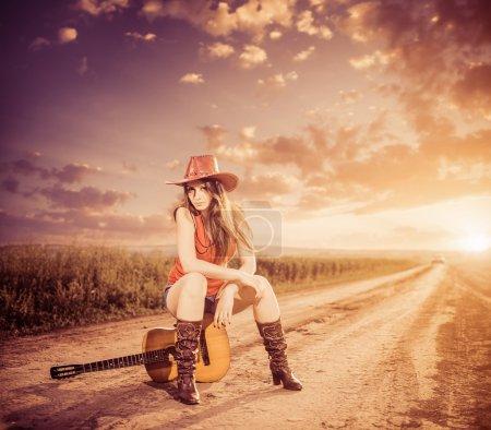 Mujer en la guitarra en el camino del atardecer