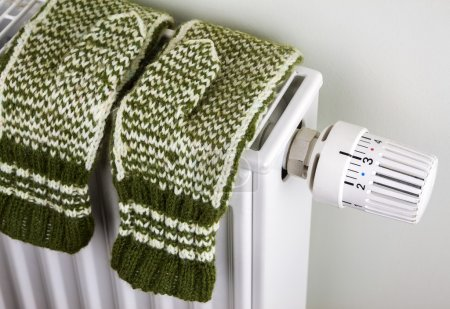 Photo for Pair of green knitted gloves drying on the radiator with thermostat - Royalty Free Image