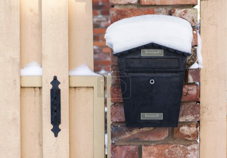 Photo for Black mailbox covered with snow outside residential house - Royalty Free Image