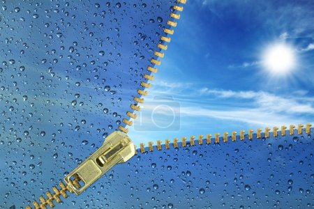 Photo for Unzipped glass with water drops revealing blue sky - Royalty Free Image