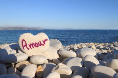 Photo pour Amour écrit sur la pierre en forme de coeur sur la plage - image libre de droit