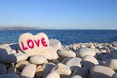 Love written on heart shaped stone on the beach