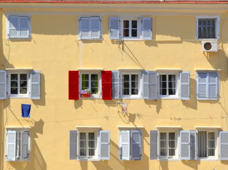 Stand out from the crowd - Being different concept, Red shutter among grey shutters
