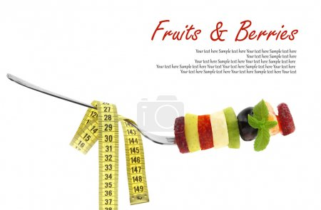 Fresh mixed slices of fruits on a fork with measuring tape