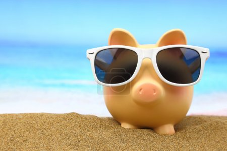 Summer piggy bank with sunglasses on the beach...