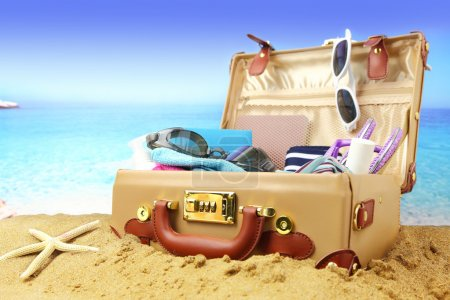 Full open suitcase on tropical beach background...