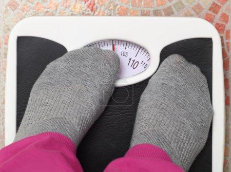 Female feet on bathroom scale