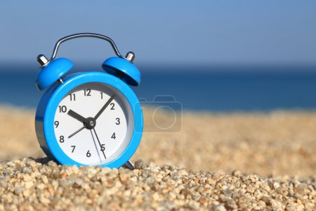 Vacation time. Alarm clock on the beach
