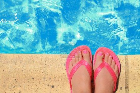 Photo pour Femmes pieds avec flip flops au bord de la piscine - image libre de droit
