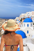 Woman in hat overlooking traditional white blue Santorini houses