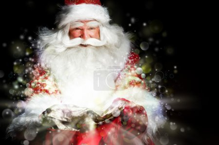 Photo for Santa sitting at the Christmas room and looking into the sack - Royalty Free Image