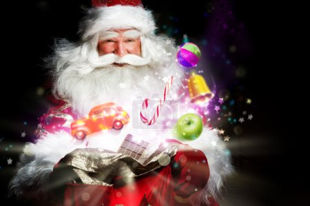 Photo for Santa Claus getting gifts and confection from his bag and showing miracle - Royalty Free Image
