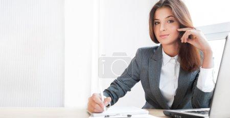 Photo pour Belle jeune femme d'affaires assise détendue à son bureau et regardant la caméra - image libre de droit