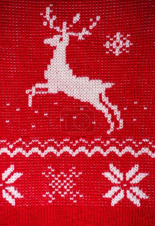 Real red knitted background with white Christmas deer and snowfl