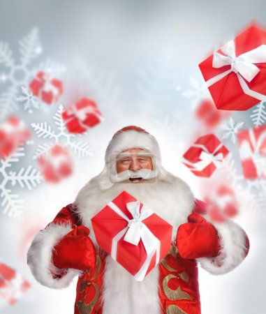 Photo for Laughing Santa Claus standing and doing magic. Gift boxes falling down around him - Royalty Free Image
