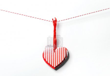 Red textured hearts hanging on white background