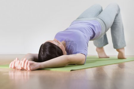 Portrait of healthy young woman practising yoga exercise on mat