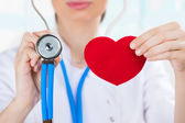 Female doctor with stethoscope holding red human heart
