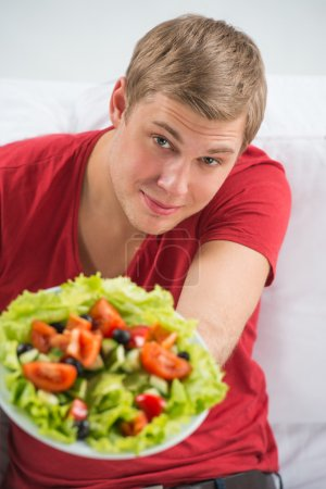 Young handsome man preparing to eat fresh healthy salad