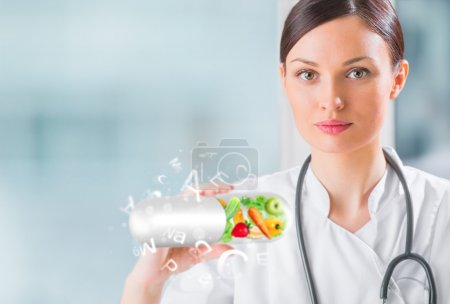 Healthy life concept. Female medical doctor holding vitamins