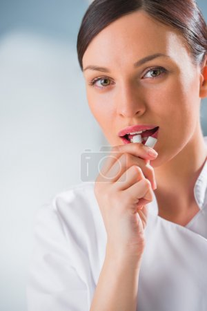 Young female dentist doctor holding chewing gum and smiling.