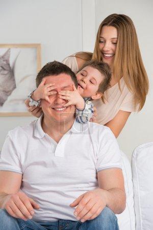 Photo pour Famille heureuse s'amuser dans le salon : fils surprenant son père en se couvrant les yeux - image libre de droit
