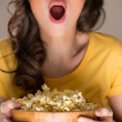 Unrecognizable woman eating popcorn at the cinema...