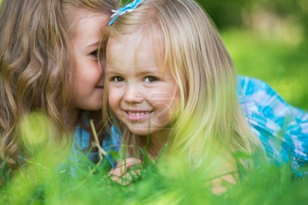 Happy children relaxing on green grass in summer park