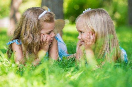 Photo pour Deux petites filles mignonnes sur la pelouse du parc - image libre de droit
