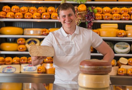 Handsome male owner of a cheese store standing with cheese piece
