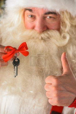 Père Noël tenant les clés de la maison ou de l'appartement neuf et les pouces levés