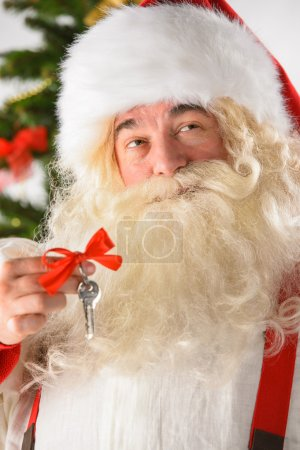 Santa Claus holding keys New year - new home concept
