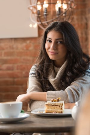 Photo for Young woman drinking coffee in a cafe indoors. Shallow depth of field. - Royalty Free Image