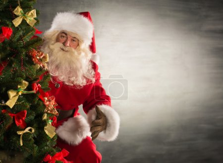 Photo for Santa Claus standing near Christmas tree. Lots of copyspace - Royalty Free Image