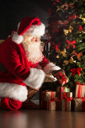 Photo for Santa putting gifts under Christmas tree in dark room - Royalty Free Image