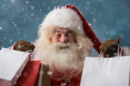 Photo for Photo of happy Santa Claus outdoors in snowfall holding shopping bags. Christmas sales and discount concept - Royalty Free Image
