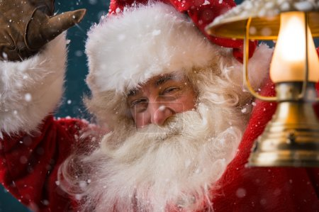 Santa Claus is holding a shining lantern while sneaking to his home