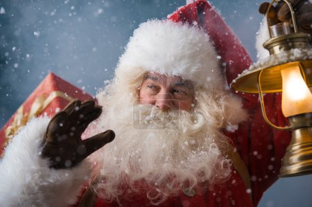 Santa Claus outdoors in snowfall lights the way with vintage lantern