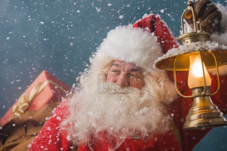Photo for Santa Claus walking on the snow with his sack of lots of gifts and lights his way with vintage lantern. Winter night with snowfall - Royalty Free Image