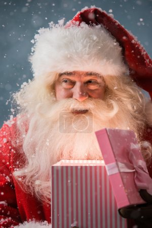 Photo for Portrait of happy Santa Claus opening gift box outdoors at North Pole. Magical light from box on his face - Royalty Free Image