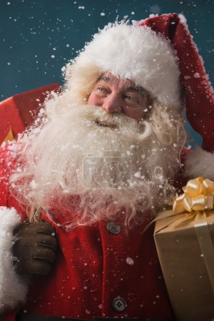 Photo for Photo of happy Santa Claus outdoors in snowfall carrying gifts to children - Royalty Free Image