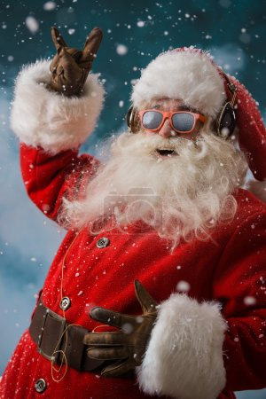 Photo for Santa Claus is listening to music in headphones outdoors at North Pole, Having fun while delivering gifts - Royalty Free Image