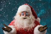 Santa Claus wearing sunglasses dancing outdoors at North Pole