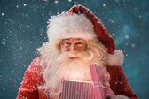 Happy Santa Claus opening his Christmas gift at North Pole