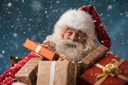 Photo for Santa Claus walking on the snow with his sack of lots of presents. Winter night with snowfall - Royalty Free Image